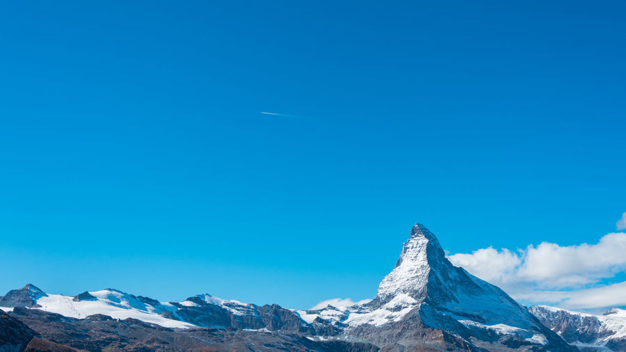 Scenic view of snowcapped mountains against clear blue sky, matterhorn, switzerland