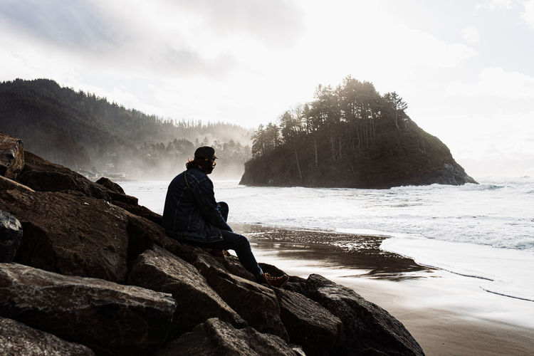 Man sitting on rock looking at mountain against sky