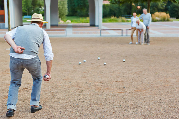 rear view of man playing with ball Ball Baseball - Sport Boccia Boule Cap Casual Clothing City Competition Couple Couples Day Elderly Focus On Foreground Friends Friendship Full Length Fun Game Group Hat Interaction Leisure Leisure Activity Lifestyle Lifestyles Males  Man Men Nursing Home Old Outdoors Outside Partnership Pensioner People Petanque Play Playing Playing Field Real People Rear View Retired Retiree Retirement Home Senior Senior Citizen  Senior Citizens Seniors Sport Standing Summer Target Team Throw Together Urban Weekend Activities Woman Women