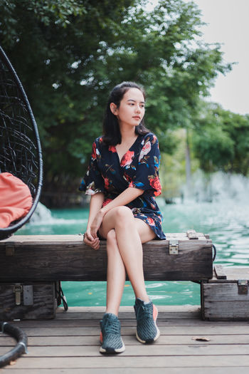 Beautiful young woman sitting on bench against lake