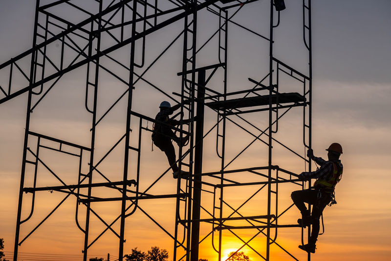 Silhouette man working at construction site against sky