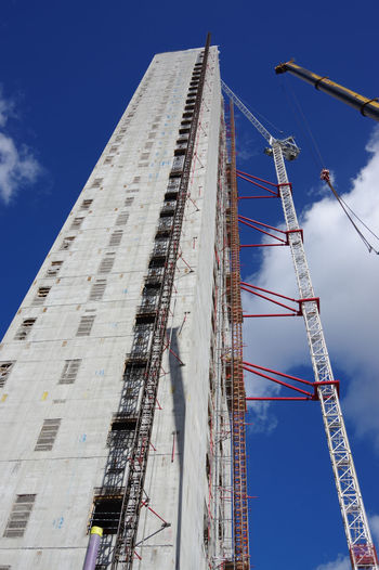 Low angle view of crane by building against blue sky