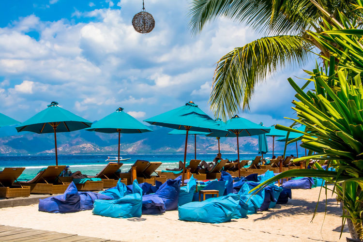 Lounge Chairs And Bean Bags With Parasols At Beach Against Cloudy Sky