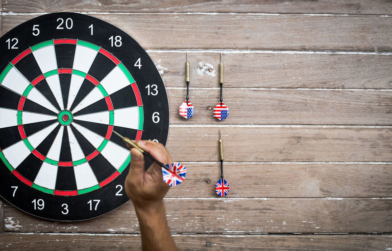 Close-Up Of Man Aiming At Dart Board
