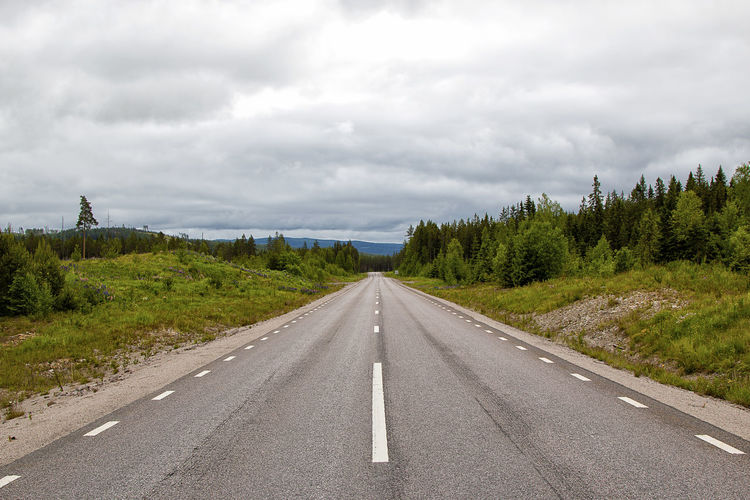 Empty road amidst trees against cloudy sky