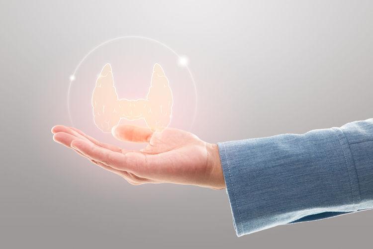 Digital composite image of hand holding illuminated light against gray background