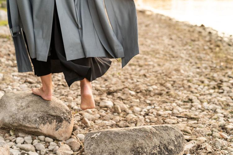 Low section of woman walking on rocks