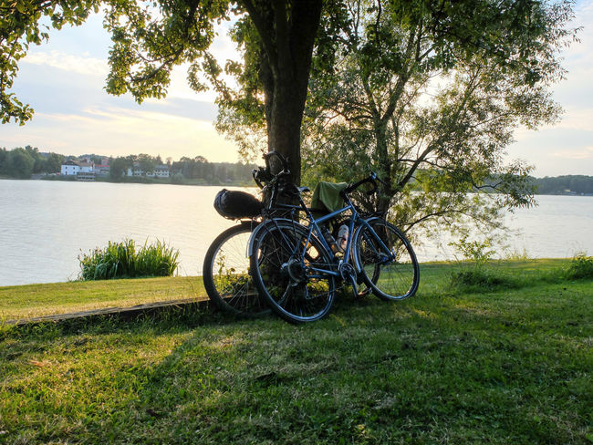 Adventure By Bike Adventure Beauty In Nature Bicycle Bike Packing Bike Touring Cyclo Travel Day Grass Growth Lake Land Vehicle Mode Of Transport Nature No People Outdoors Scenics Sky Stationary Tranquil Scene Tranquility Transportation Tree Tree Trunk Water