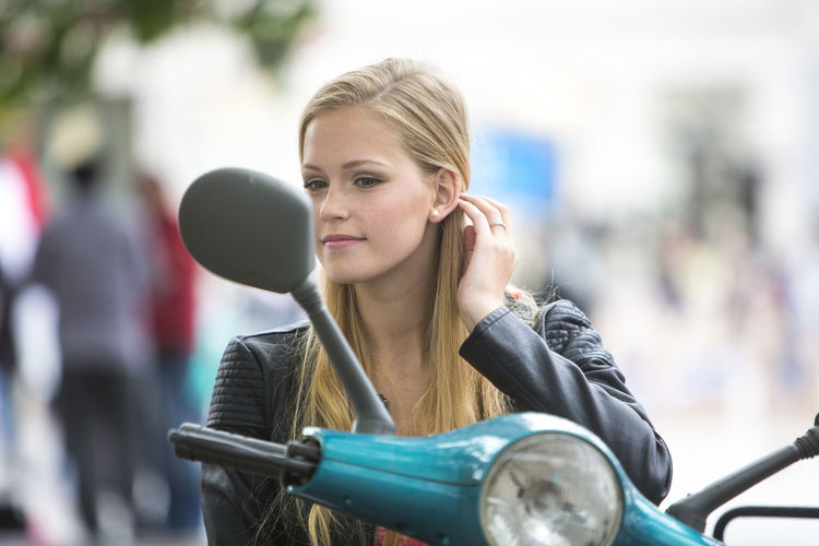 Young woman looking in side-view mirror of motor scooter