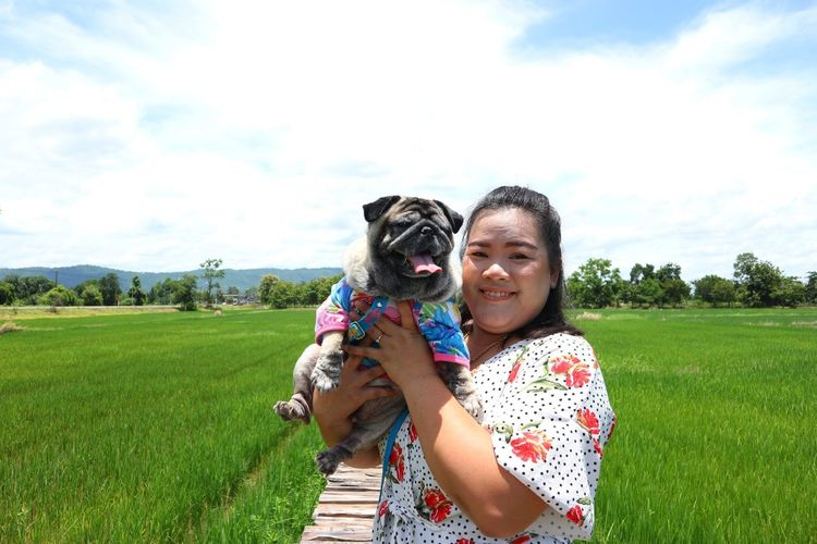 Portrait of smiling woman with dog standing on paddy field