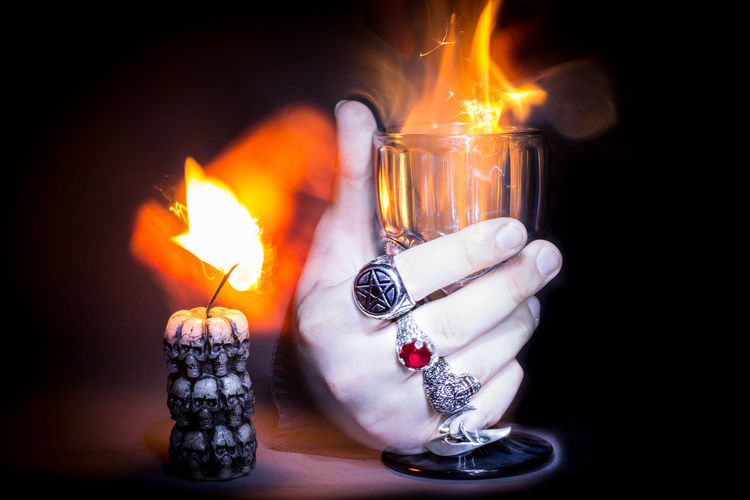 Cropped Hand Holding Fire In Wineglass On Table