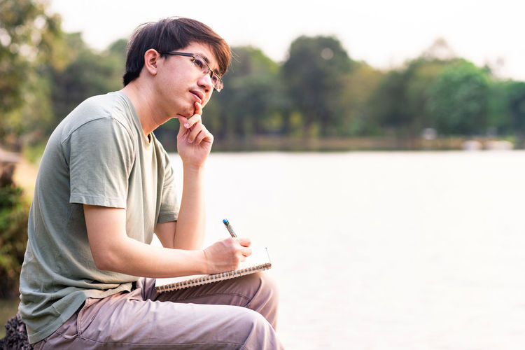 Young man looking away while sitting with book and pen by lake