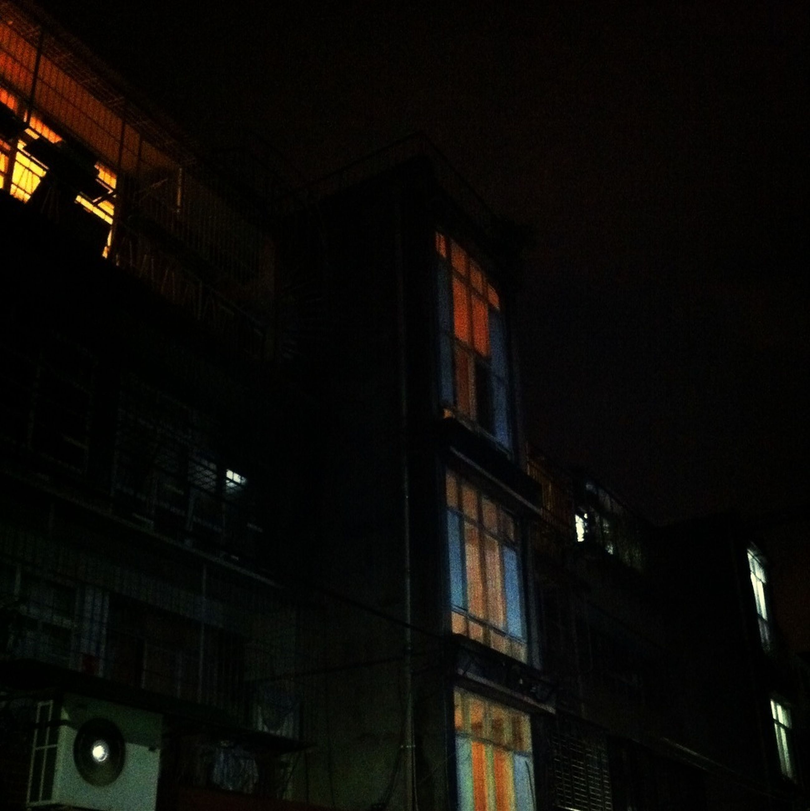 architecture, built structure, building exterior, night, illuminated, low angle view, window, building, city, residential building, dark, residential structure, no people, lighting equipment, exterior, outdoors, house, sky, modern, facade