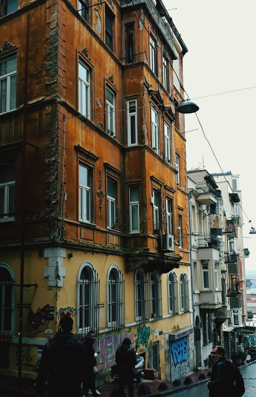 building exterior, built structure, architecture, city, building, real people, residential district, window, group of people, sky, men, people, lifestyles, day, city life, nature, street, women, clear sky, outdoors, apartment