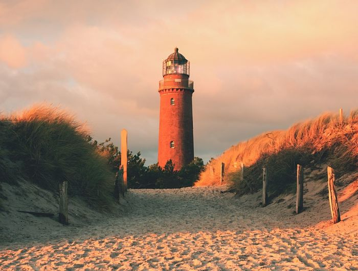 Historical lighthouse, dunes and pine tree. warning light, dark sky. lighthouse tower from red brick