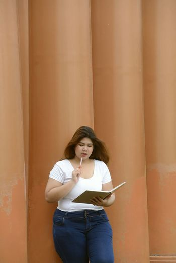 Young woman reading book by columns