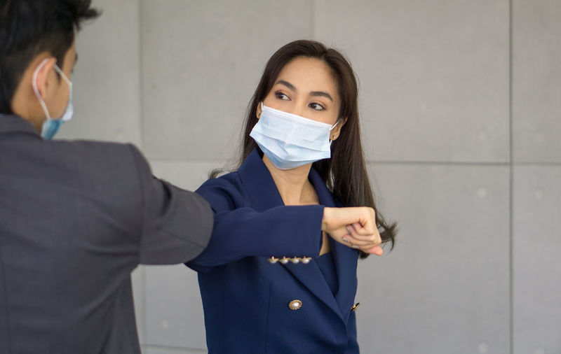Smiling business person wearing flu mask gesturing against wall