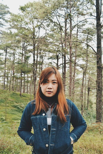 Portrait of young woman standing against in forest