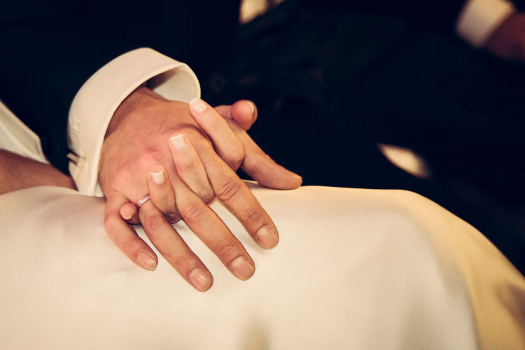 Midsection Of Newly Wed Couple Holding Hands