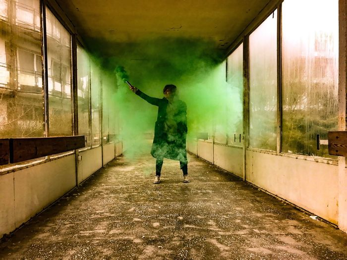 Woman With Green Smoke Grenade In Abandoned Building