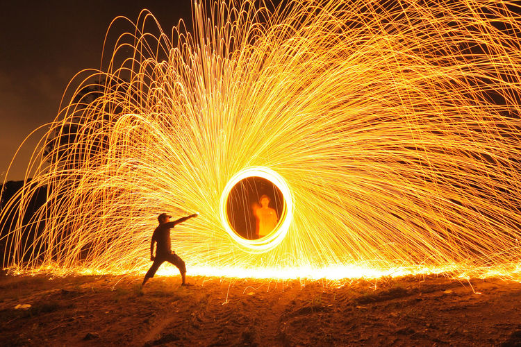 Silhouette Adult Adults Only Blurred Motion Burning Circle Danger Fireball Firework Display Full Length Glowing Heat - Temperature Illuminated Long Exposure Men Motion Night One Man Only One Person Only Men Performing Arts Event Skill  Speed Spinning Swirl Wire Wool Paint The Town Yellow Business Stories