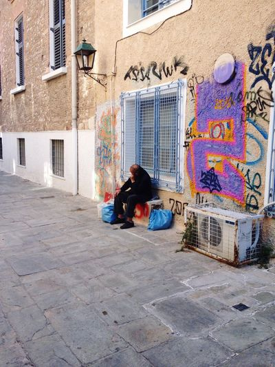 The Crisis Real People Building Exterior Full Length One Person Architecture Sitting Outdoors Built Structure City Day People Adults Only Adult Crisis Greek Crisis Graffiti