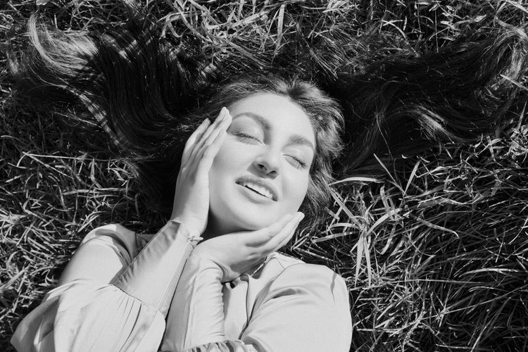 High angle view of smiling girl lying on grass