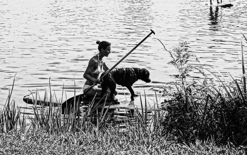 Girl With Her Dog On A Surfboard Sitting Stand Up Paddling water Lake Grass Lakeshore Relaxation Nature Outdoors Non-urban Scene Kinzigsee Germany🇩🇪 Starting A Trip Monochrome Photography