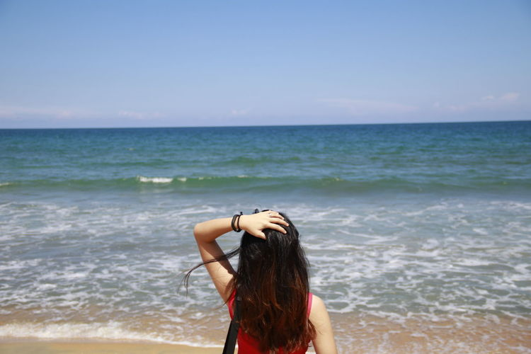 Young woman at beach against sky