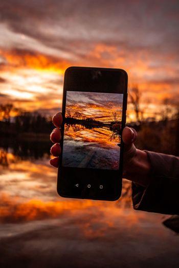 Hand holding smart phone against orange sky