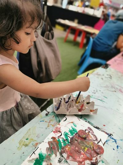 High angle view of cute girl painting on table