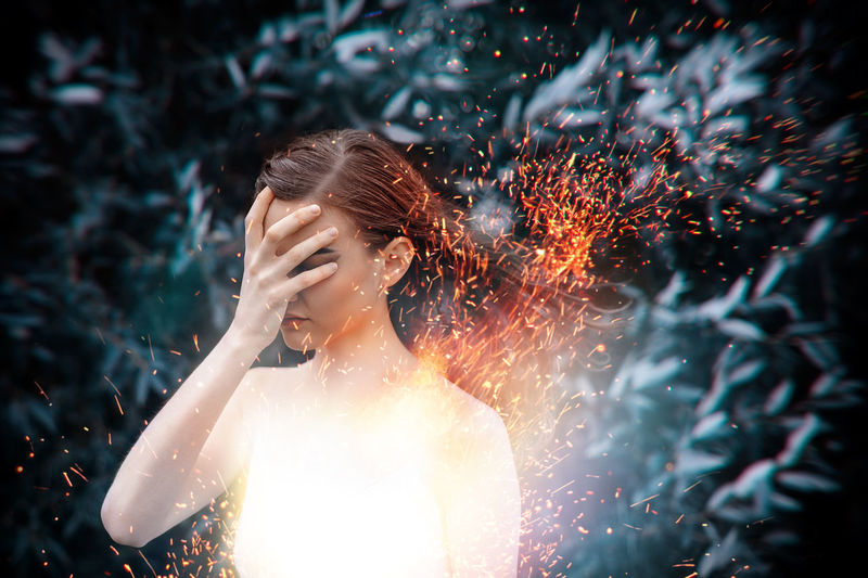 Close-up of woman standing against sparks