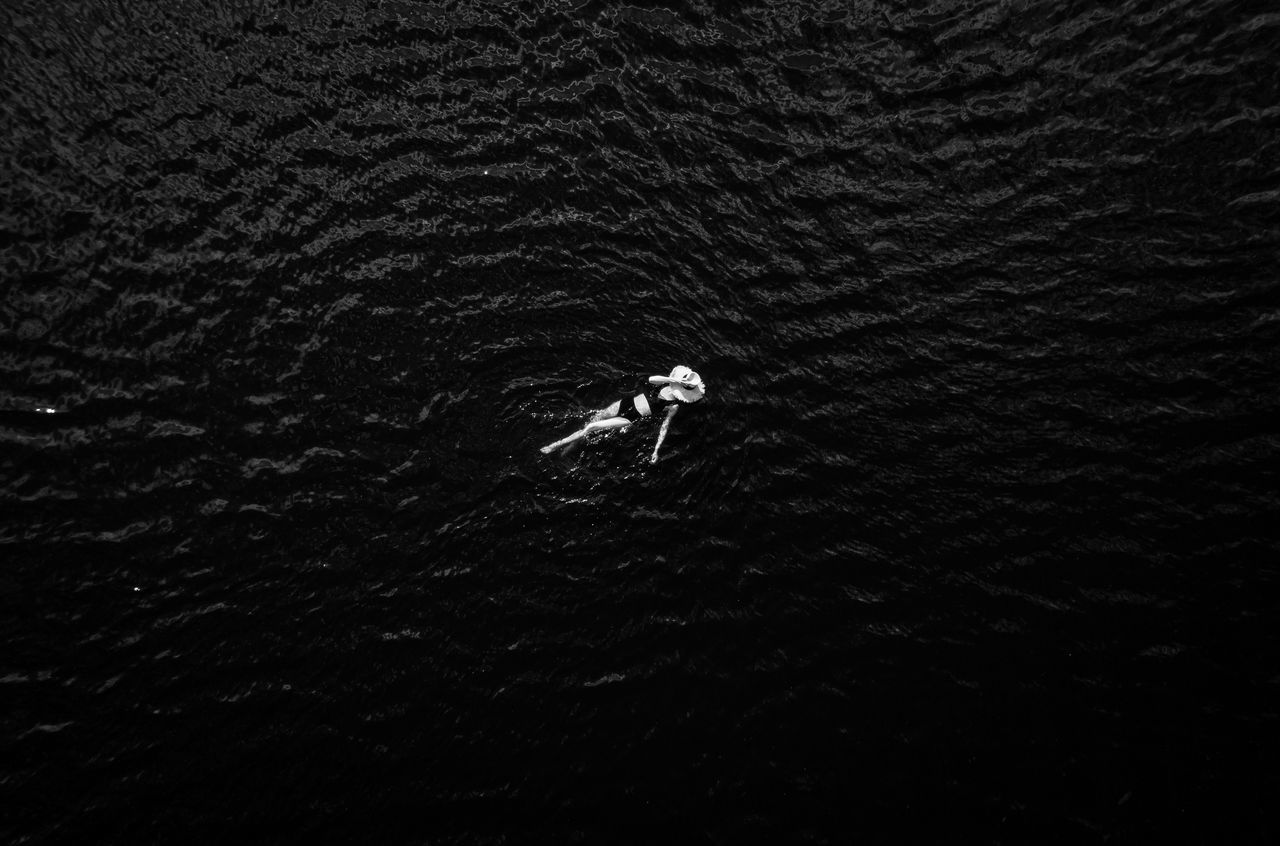 HIGH ANGLE VIEW OF MAN SURFING ON WATER