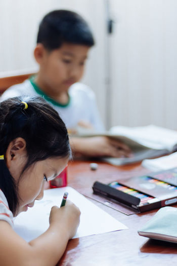 Homework Education Child Childhood Indoors  Student Table Indoors  Girls Women Females Real People People Holding Males  Boys Men Headshot Concentration Learning Paper Art And Craft Selective Focus Studying Colored Pencil