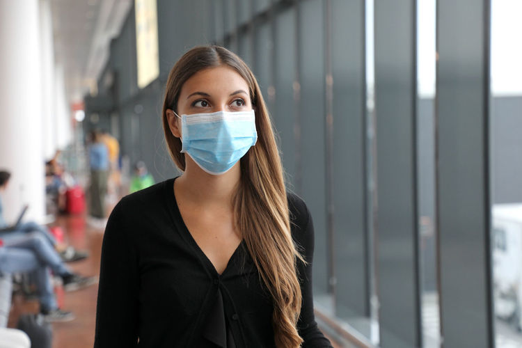Woman wearing mask looking away in airport