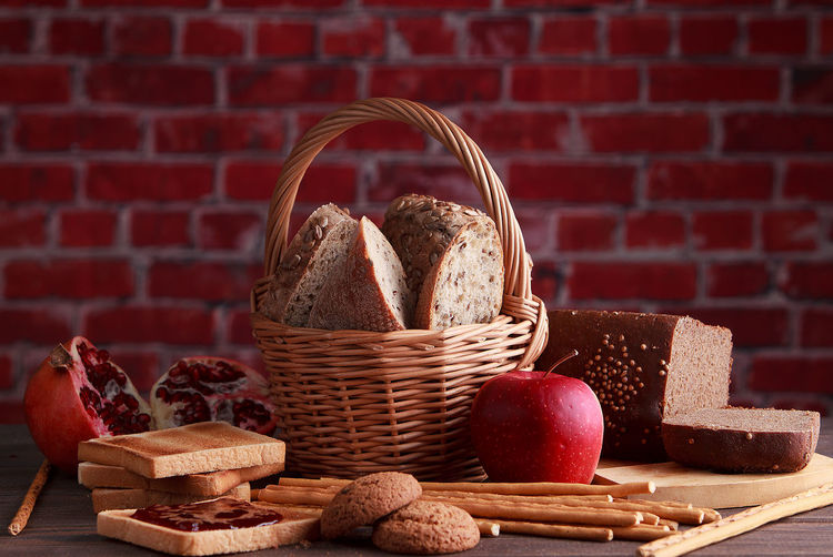 Close-up of wicker basket on table against brick wall