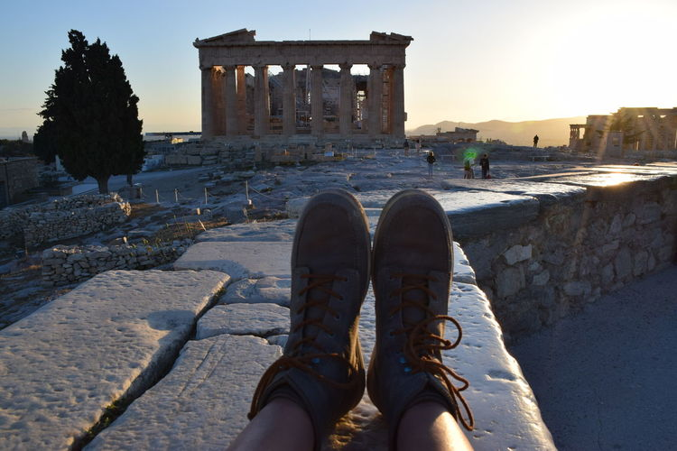 Low section of person legs by parthenon against clear sky during sunset