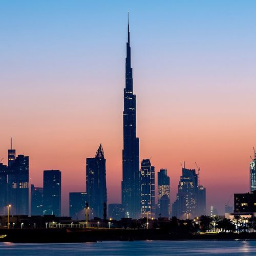 Illuminated Burj Khalifa Amidst Buildings In City Against Sky During Sunset