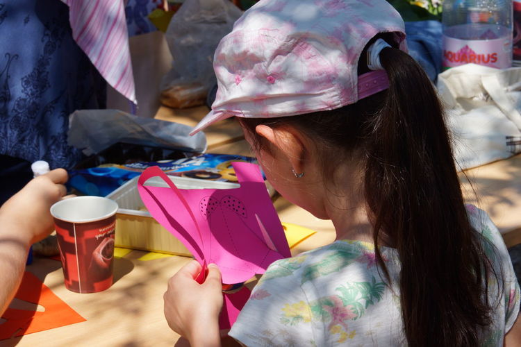 Close-up of girl cutting paper in sunny day