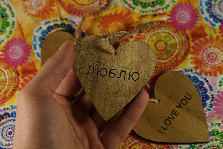 Cropped Hand Of Woman Holding Heart Shape With Text Over Table