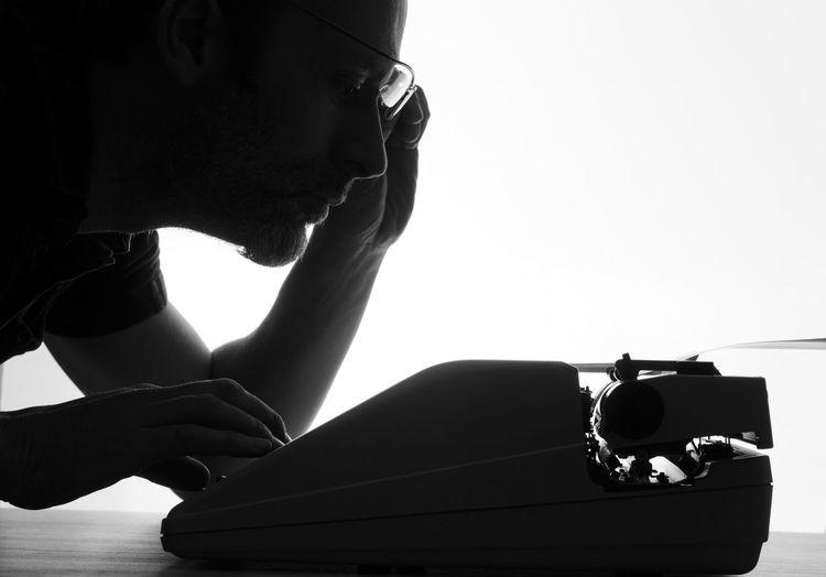 Man typing on typewriter against white background