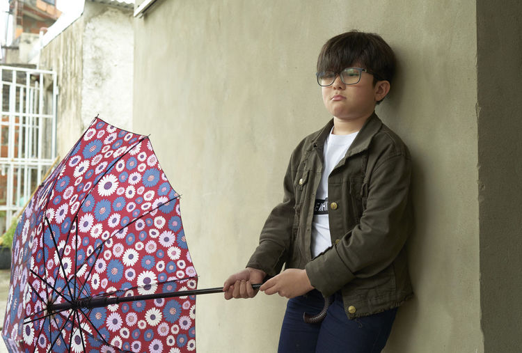Boy with glasses coming out with umbrellas on rainy days