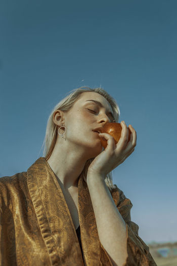 Low angle view of woman with eyes closed eating apple against clear sky