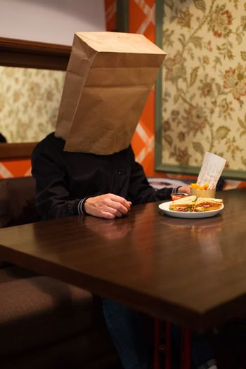 Man with paper bag on face while having sandwich in restaurant