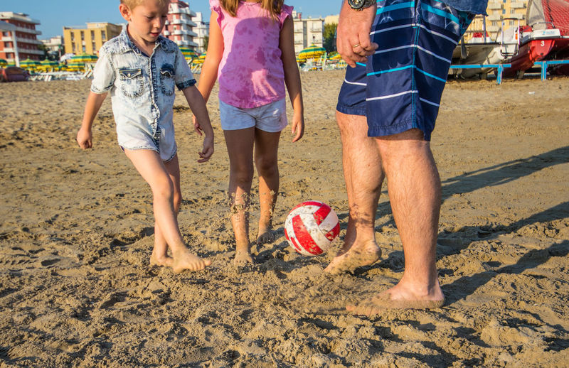 Father playing soccer with son and daughter on sand at beach