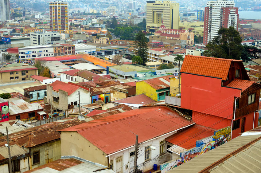 VALPARAISO, CHILE - MAY 28: The bright colors of the old town shine above the modern skyscrapers in Valparaiso, Chile on May 28, 2014 America Architecture Art Building Chile City Colorful Construction Culture Harbor Heritage Hill Latin Old Port Residential  South Structure Tourism Unesco Urban Valparaiso, Chile Valparaíso View World