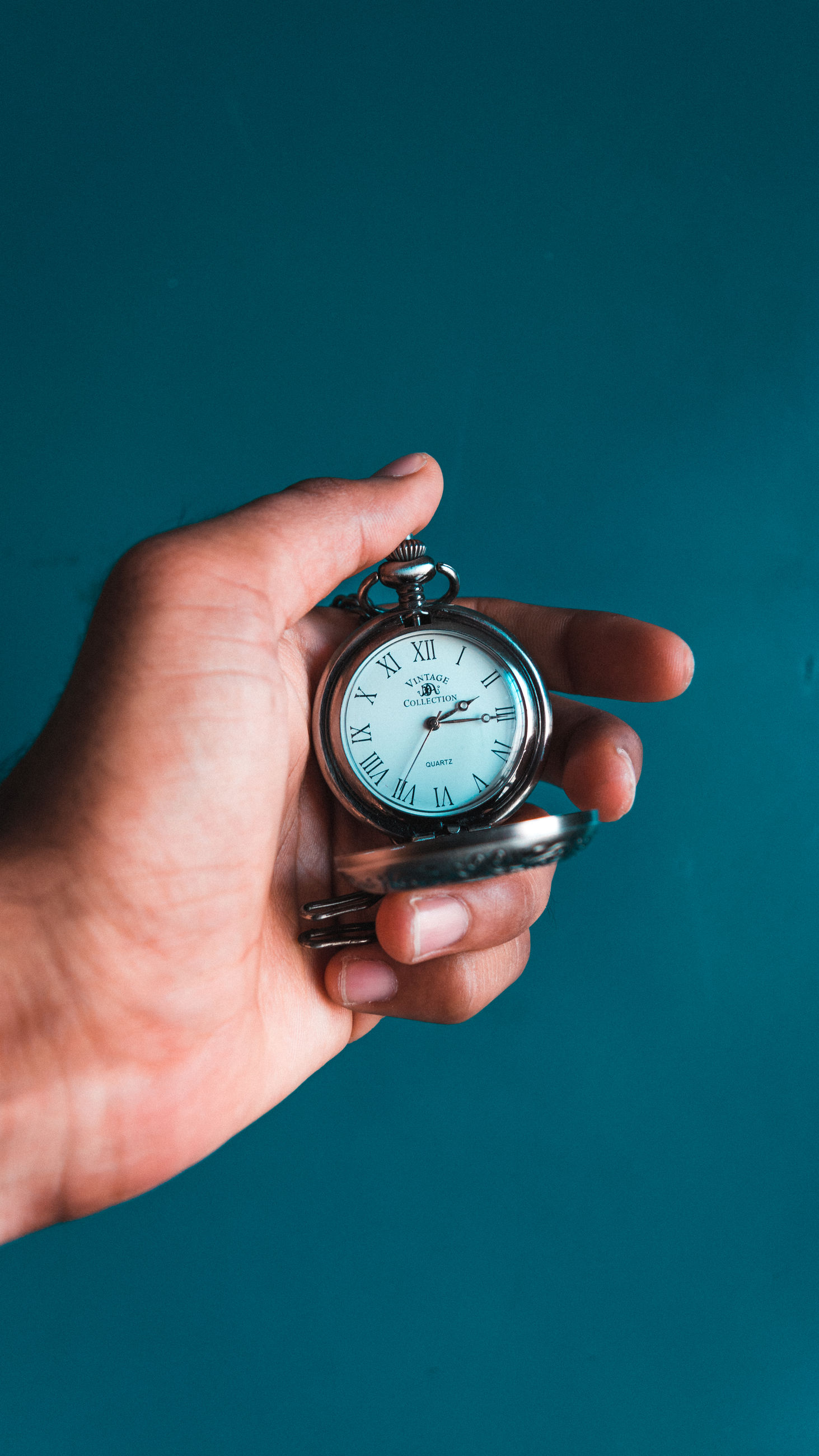 human hand, hand, human body part, time, holding, one person, clock, watch, real people, body part, indoors, colored background, studio shot, blue, lifestyles, instrument of time, blue background, close-up, unrecognizable person, finger, pocket watch, clock face, personal accessory, stopwatch