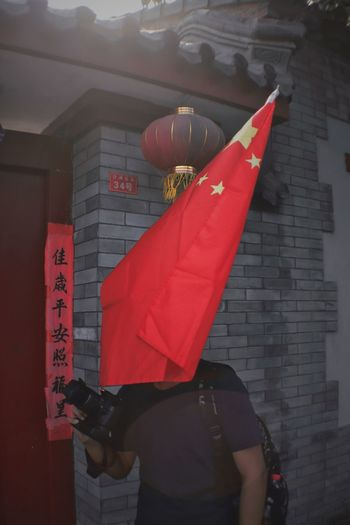Midsection of woman holding red lantern against wall