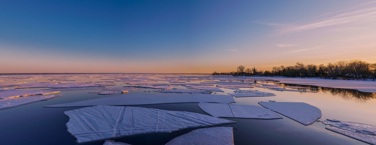Scenic view of frozen lake against sky during sunset