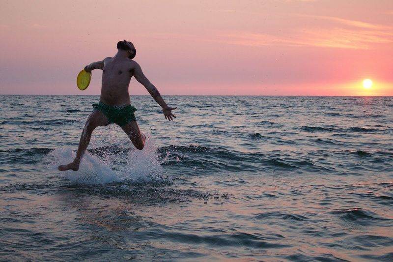 Playful shirtless man jumping in sea against orange sky